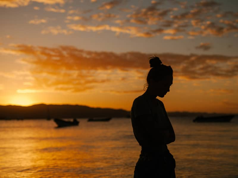 woman with depression against sunset